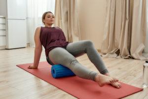 Junge Frau zeigt, wie du mit Faszientraining gegen Knieschmerzen vorgehen kannst.