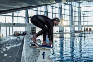 Das Bild zeigt einen Schwimmer im Ganzkörperanzug auf dem Startblock im Schwimmbad