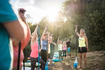 Das Bild zeigt eine Gruppe von Julia Klesse bei der Einweisung vor dem SUP Yoga.
