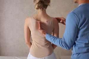 Das Bild zeigt einen Faszientherapeuten bei der sanften Faszientherapie am Rücken einer jungen Frau