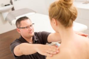 Das Foto zeigt Faszientherapeut Patrick Nehmzow bei der Faszienuntersuchung als Teil der Faszientherapie