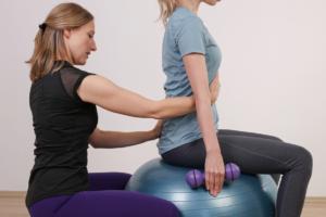 Das Bild zeigt eine Frau bei der Haltungskorrektur einer auf einem Sitzball sitzenden Frau.