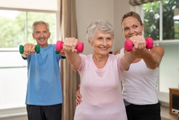 Das Foto zeigt strahlende Senioren bei Übungen mit Anleitung in einem Kurs