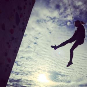 """Das Bild zeigt eine Frau am Kletterseil hängen als Beispiel der vielseitigen positiven Wirkung des Kletterns nicht nur aus der Physiotherapie-Sicht hier im Beitrag """"Therapeutisches Klettern"""""""