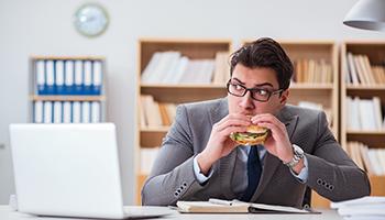 Das Foto zeigt einen Mann beim Snack im Büro als Sinnbild wie die Progressive Muskelentspannung gegen emotionales Essen helfen kann.