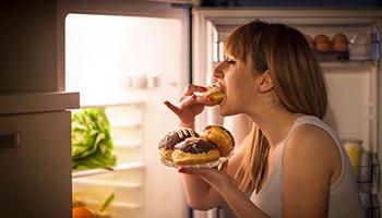 Das Foto zeigt eine Frau beim Mitternachtssnack am Kühlschrank als Sinnbild wie die Progressive Muskelentspannung gegen emotionales Essen helfen kann.