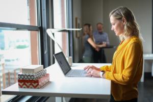 Das Foto zeigt eine Frau mit Laptop an einem Stehtisch als Sinnbild für Bewegung am Arbeitsplatz