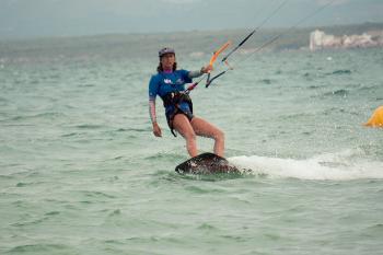 Das Foto zeigt eine junge Frau beim entspannten Kitesufen mit einer Hand um die Kraftübertragung über das Trapez zu verdeutlichen