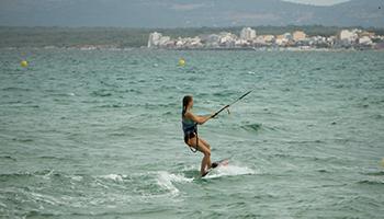 Das Foto zeigt eine Jugendliche beim Kitesurfen im warmen Mittelmeer