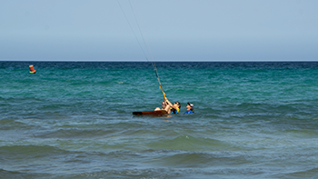 Das Foto zeigt einen Instructor der einem Jugendlichen den Start beim Kitesurfen beibringt
