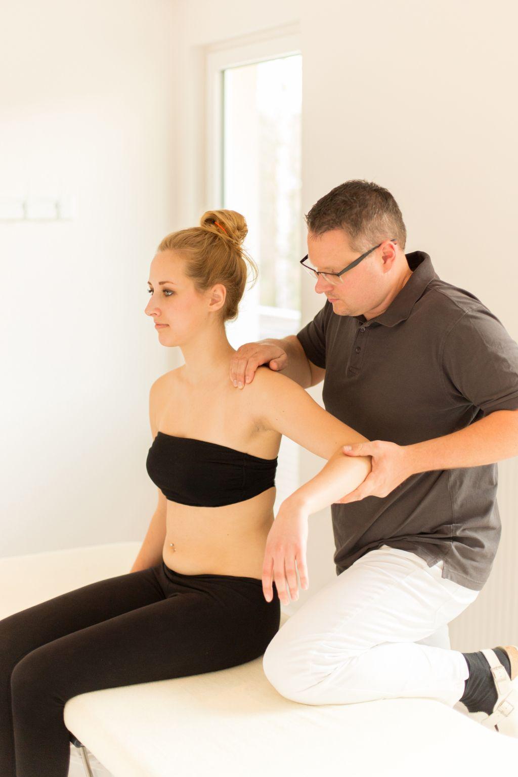 Das Foto zeigt Faszientherapeut Patrick Nehmzow bei der Körperbehandlung als Teil der Faszientherapie zur Schmerzbehandlung