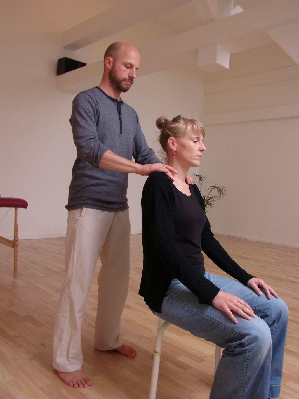 Das Foto zeigt den Alexander-Technik-Lehrer Christoph Bacher bei der Bearbeitung der Schulterpartie einer auf einem Stuhl sitzenden Frau