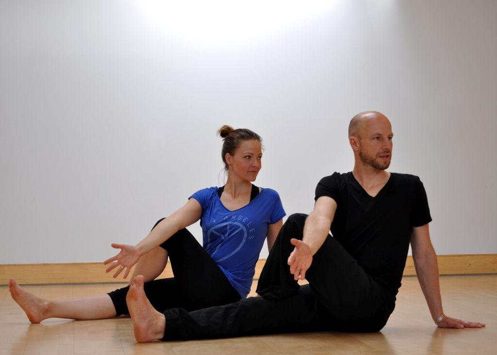 Das Bild zeigt den Alexander-Technik-Lehrer Christoph Bacher bei einer Yoga-Übung mit einer Frau