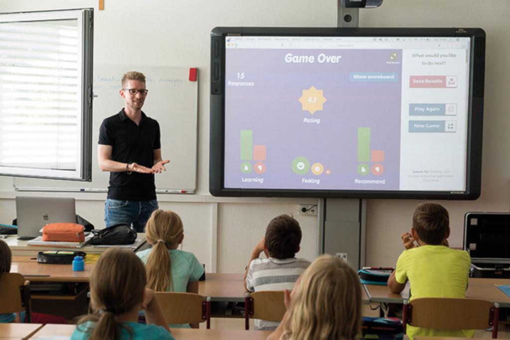 Das Foto zeigt einen Lehrer beim Unterricht mit jungen Kindern als Sinnbild für betriebliches Gesundheitsmanagement in Schulen