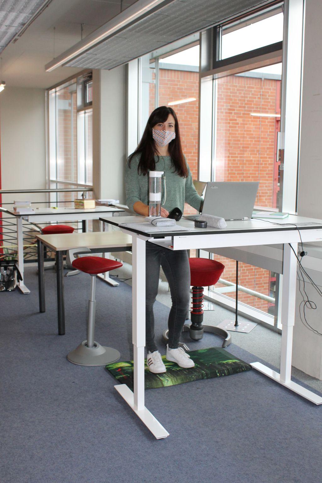 Das Foto zeigt die Studienleiterin an einem bewegungsaktivierten Lernarbeitsplatz in der Bibliothek der Universität Bayreuth