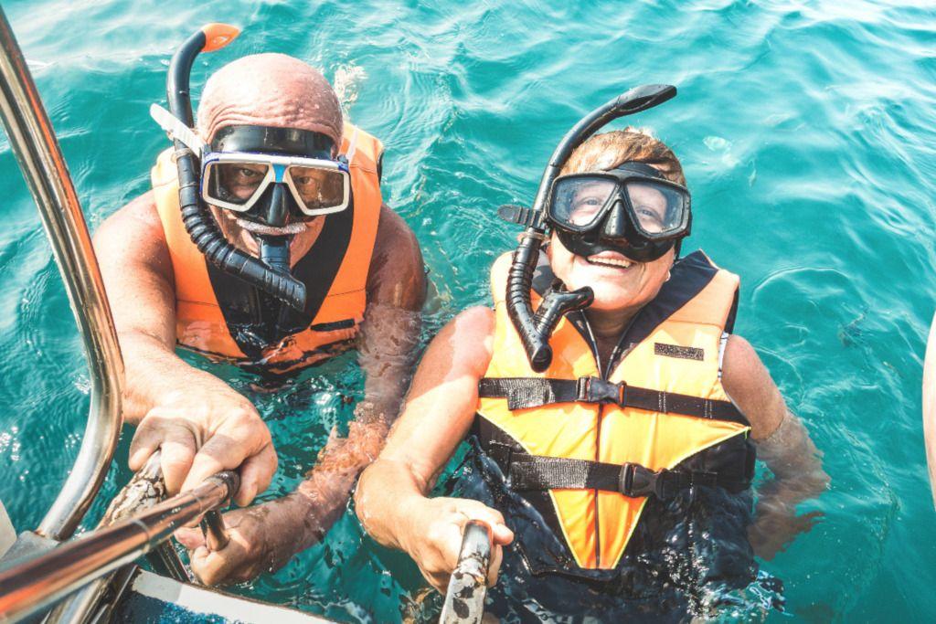 Das Bild zeigt zwei lachende Menschen mit Taucherausrüstung im warmen Meer als Sinnbild für den Sportgenuss bei Aktivreisen und Präventionsreisen zur persönlichen Gesunderhaltung