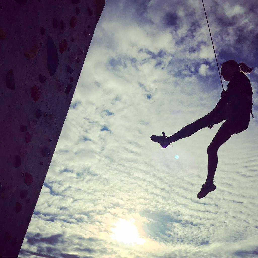 Das Bild zeigt eine Frau am Kletterseil hängen als Beispiel der vielseitigen positiven Wirkungen des Kletterns nicht nur aus der Physiotherapie-Sicht hier im Beitrag Therapeutisches Klettern