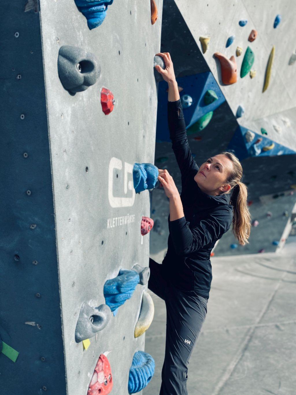 Das Bild zeigt eine Frau an einer Kletterwand als Beispiel des Muskeltrainings der Physiotherapie bei dem Greifen der Haltegriffe hier im Beitrag Therapeutisches Klettern