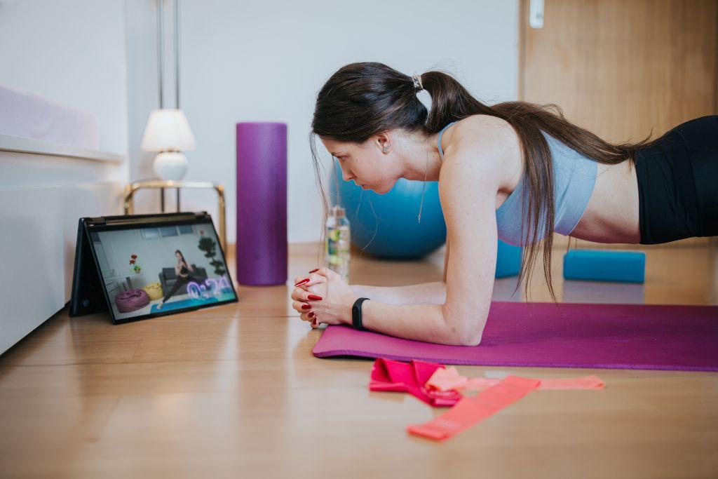 Das Foto zeigt eine junge Frau beim Faszientraining auf einer Matte mit Videoanleitung auf einem Tablet.