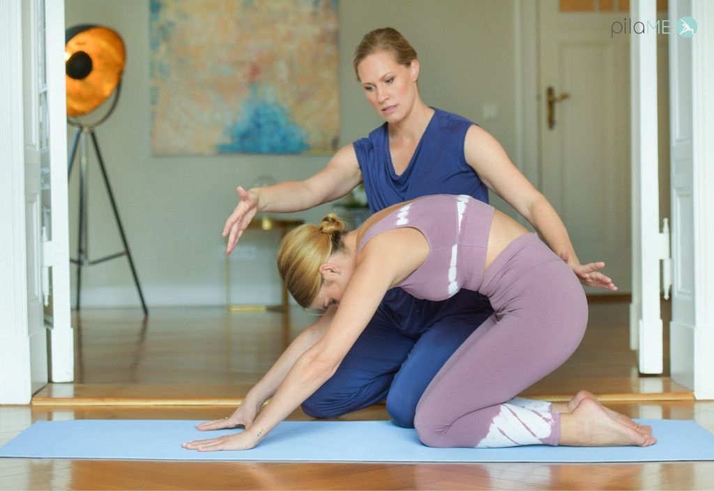 Das Foto zeigt zwei Frauen bei einer angeleiteten Dehnübung um typische Übungen im Online Präventionskurs Pilates zu veranschaulichen