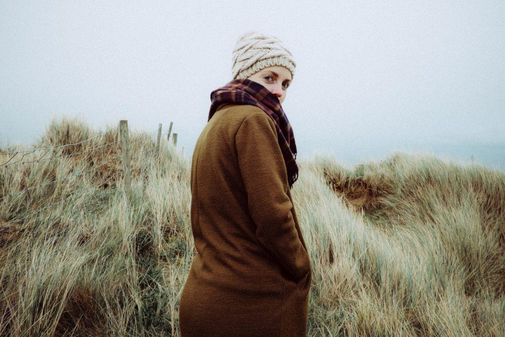Das Bild zeigt eine Frau beim Spazierengehen in der Düne als weiteren Aspekt zur Bedeutung der richtigen Ernährung für das Immunsystem