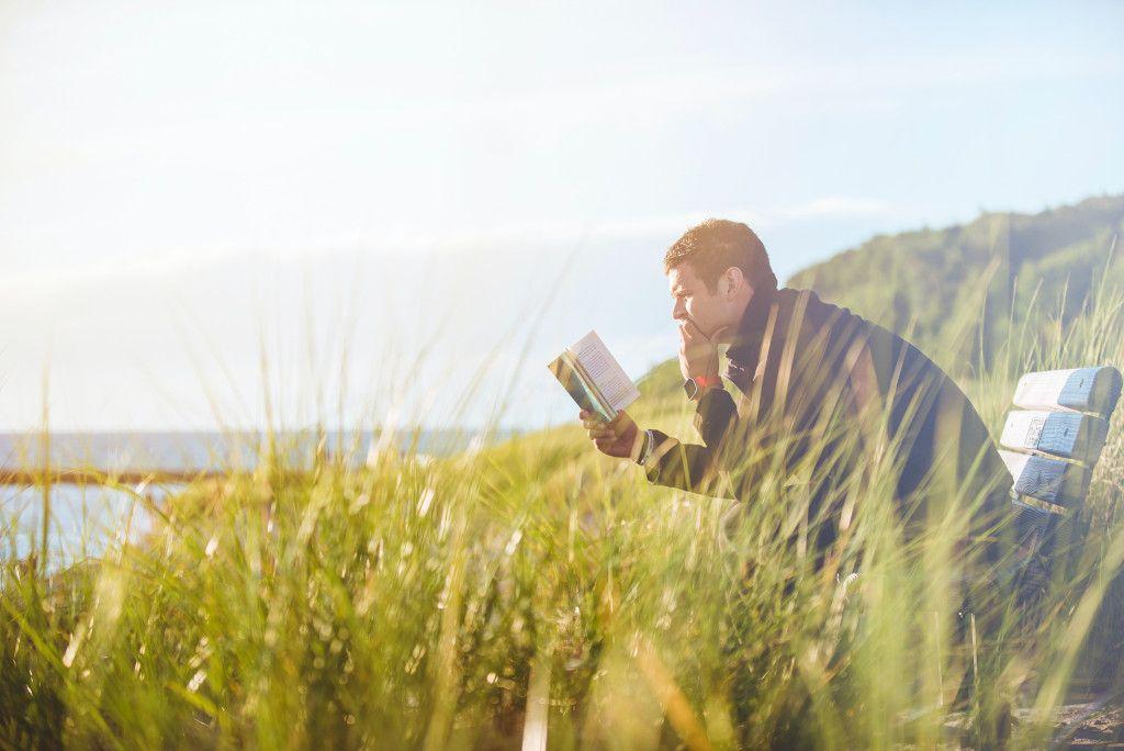 Das Bild zeigt einen Mann beim entspannten Lesen in der Natur als weiterem Aspekt zur Bedeutung der richtigen Ernährung für das Immunsystem