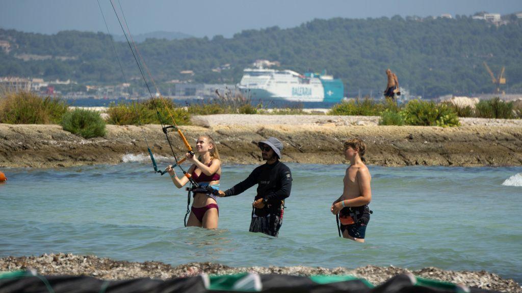 Das Foto zeigt einen Instructor der zwei Jugendlichen im MIttelmeer den Umgang mit dem Drachen beim Kitesurfen beibringt