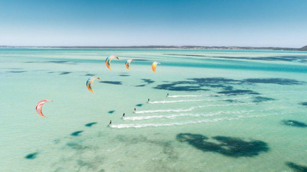 Das Foto zeigt eine Gruppe von Menschen beim Kitesurfen in klarem Wasser als Sinnbild für den Genuss der schönen Natur bei diesem Wassersport