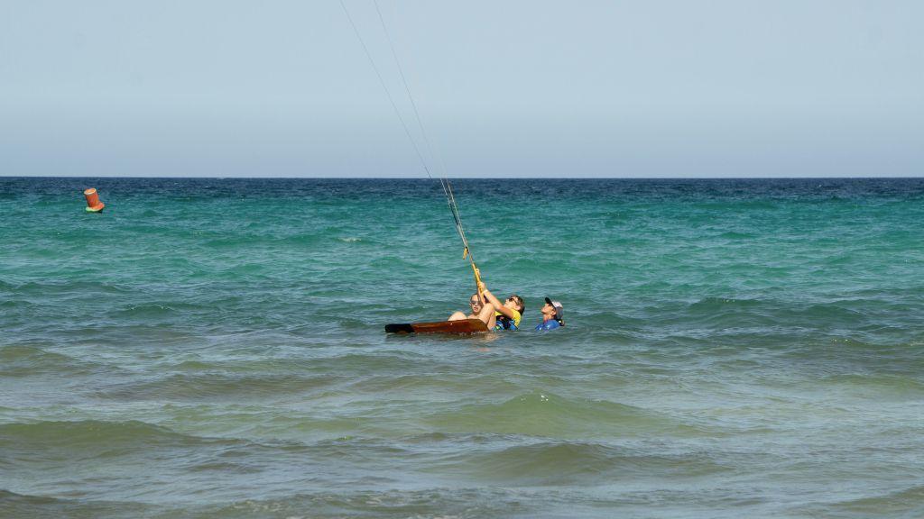 Das Foto zeigt einen Instructor der einem Jugendlichen den Wasserstart beim Kitesurfen beibringt