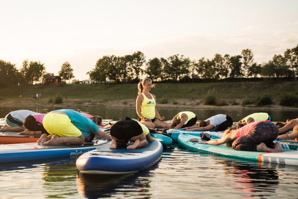 Das Bild zeigt eine Gruppe von Julia Klesse beim SUP Yoga in der Abenddämmerung.
