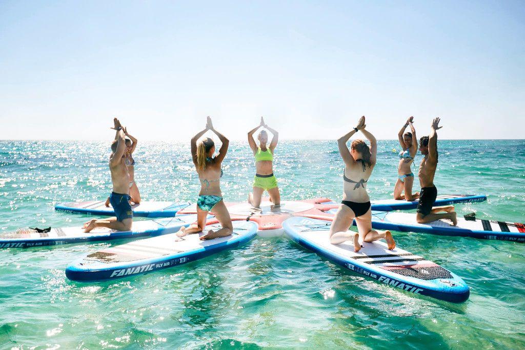 Das Bild zeigt eine kleine Gruppe beim SUP Yoga auf dem Wasser im Sonnenschein.
