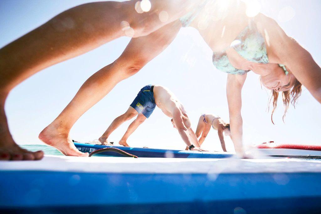 Das Bild zeigt Teilnehmer bei einer SUP Yoga Übung auf dem Board.